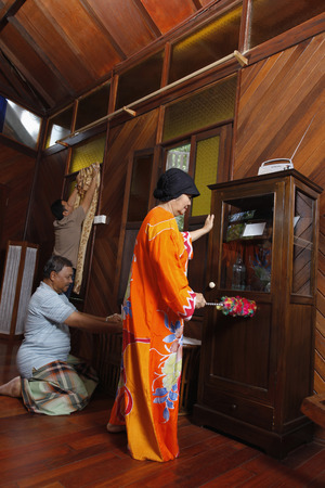 putting up: Senior woman cleaning the house, senior man arranging greeting card and man putting up curtain