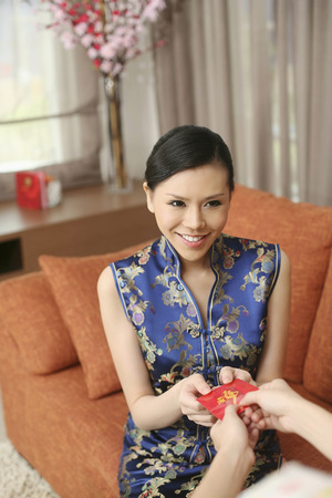 Receiving: Woman in cheongsam receiving red packet