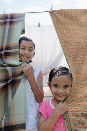 sarong: Girls hiding behind sarong on clothesline