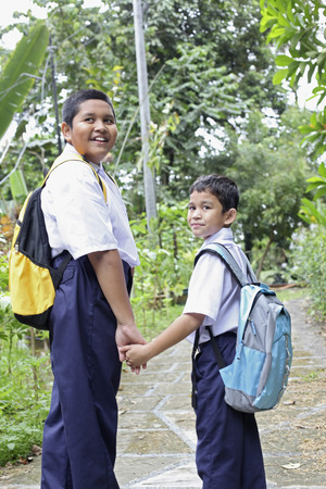 malay village: Boys in school uniforms holding hands