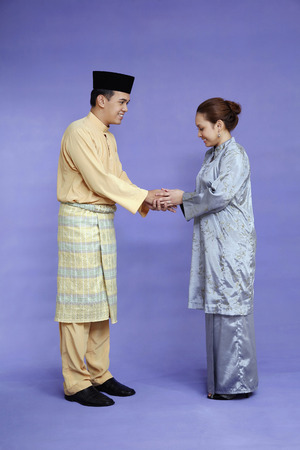 traditional clothing: Man and woman in traditional clothing greeting each other