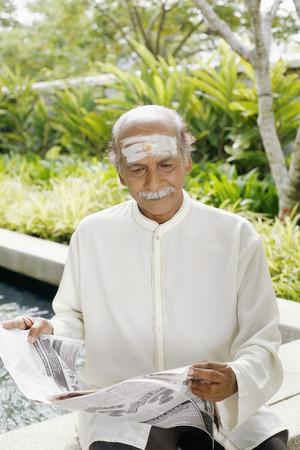 kurta: Senior man reading newspaper