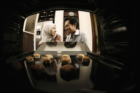 Man feeding woman cookie, view from inside the oven 免版税图像