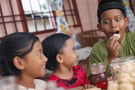 Kinder genießen traditionelle Plätzchen, Jungen machen lustiges Gesicht LANG_EVOIMAGES