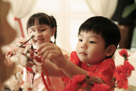 Boy and girl decorating flowers at home