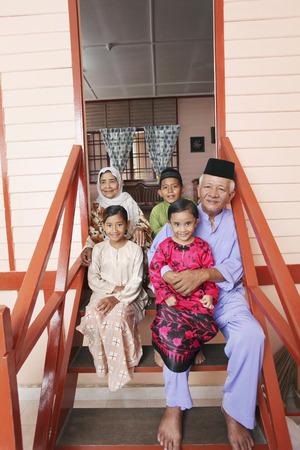 Älterer Mann und Frau mit ihren Enkeln zu Tür sitzen