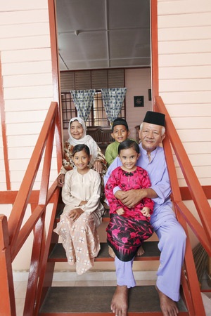 Senior man and woman with their grandchildren sitting at doorway