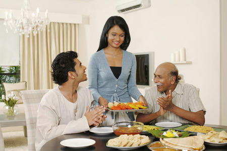 Woman serving food, man and senior man clapping hands happily