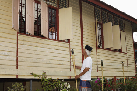 Boy waving to senior man from the house window