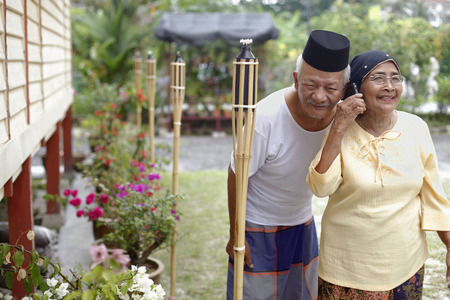 Senior woman talking on the phone while senior man is listening from the side