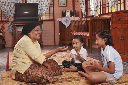 game viewing: Senior woman playing traditional game with grandchildren