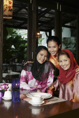 Women posing and smiling in restaurant LANG_EVOIMAGES