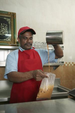 tarik: Man preparing iced teh tarik, take-away LANG_EVOIMAGES