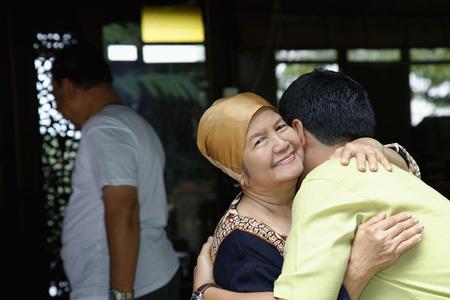 three people only: Man hugging senior woman