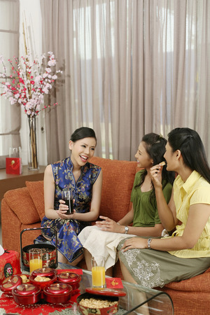 three people only: Women talking while enjoying traditional cookies during Chinese New Year LANG_EVOIMAGES
