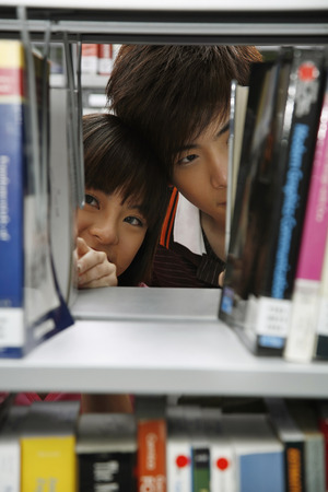 woman searching: Man and woman searching for books in the bookshelf