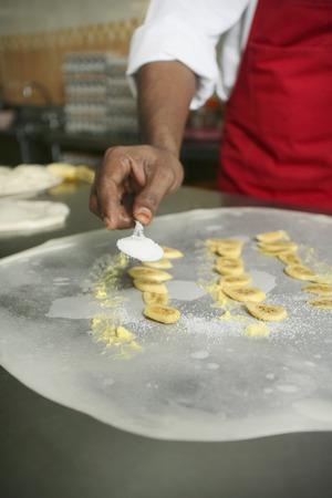 sprinkling: Man sprinkling sugar onto flattened dough and banana slices, making roti pisang