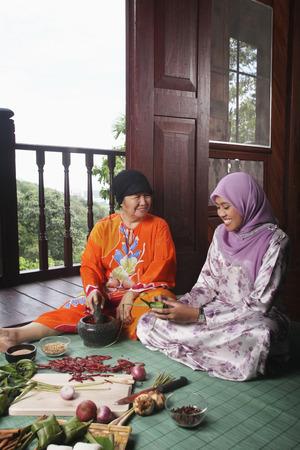 pounding: Senior woman pounding chilli while young woman wrapping ketupat