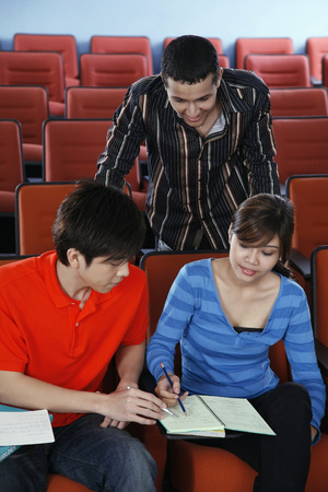 three people only: Men and woman having discussion in the lecture hall
