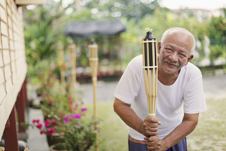 Senior man setting up bamboo torches around the house Stock Photo