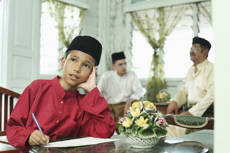 Boy thinking while writing greeting card, man and senior man chatting in the background