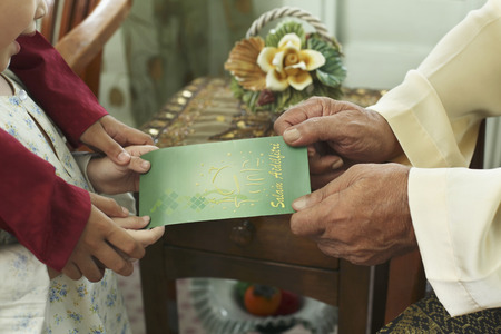 Boy and girl giving greeting card to senior man Stock Photo