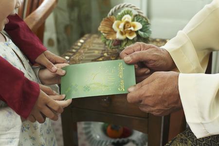 Jongen en meisje geven wenskaart naar senior man Stockfoto