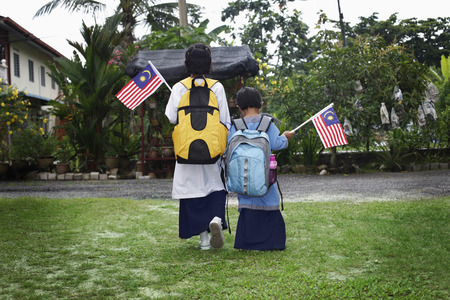 Girls walking to school with flags in their hands