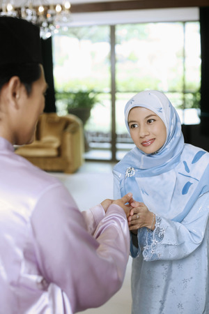 Woman greeting man during Hari Raya