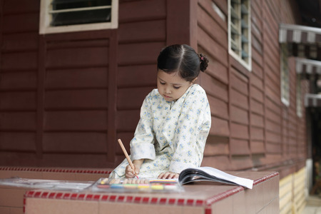 malay village: Girl colouring her book