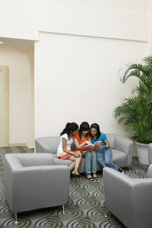 Three women reading a book together LANG_EVOIMAGES