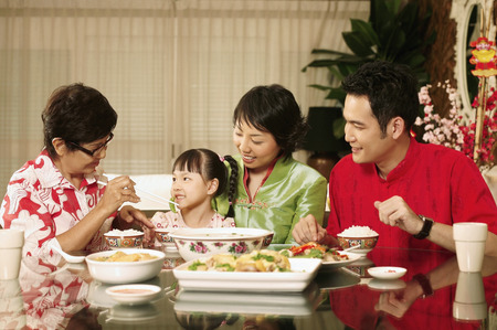 Senior woman feeding girl, man and woman watching