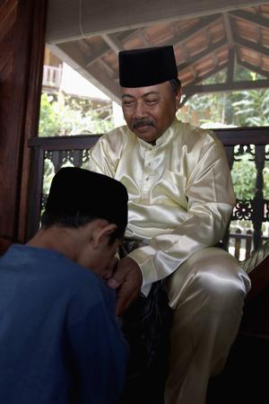 Boy greeting senior man