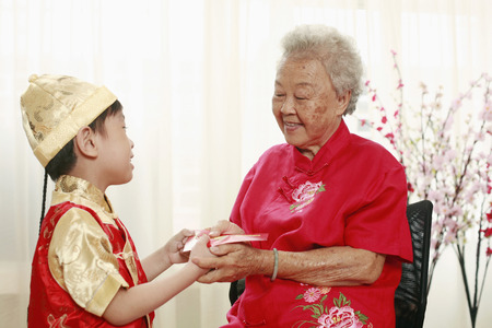 red packet: Senior woman giving boy a red packet