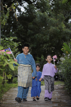 three people only: Boys and girl holding hands and running with flags