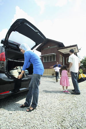 Woman keeping luggage in the car trunk, boy running towards senior man in the background
