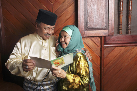 Senior woman reading greeting card while talking on the phone, senior man beside her