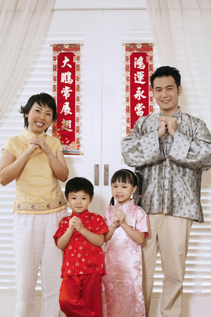traditional clothing: Couple and their children in traditional clothing showing greeting gestures