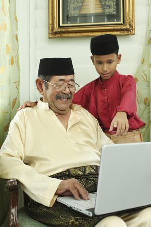 Senior man using laptop, boy watching LANG_EVOIMAGES