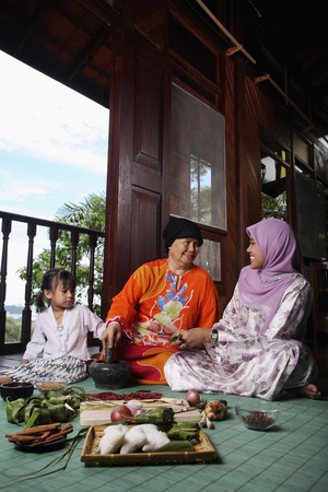 Senior woman pounding chilli while young woman wrapping ketupat, girl watching