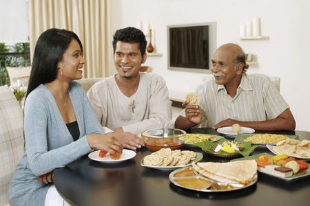 Senior man having lunch together with his son and daughter Stock Photo