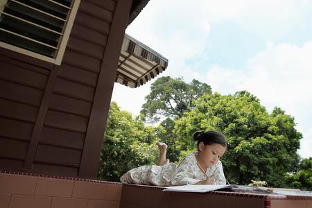 lying forward: Girl lying forward while colouring her book