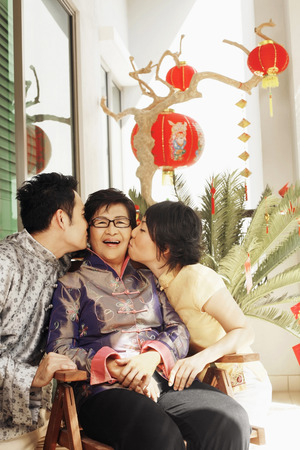 peck: Man and woman giving senior woman a peck on her cheek LANG_EVOIMAGES