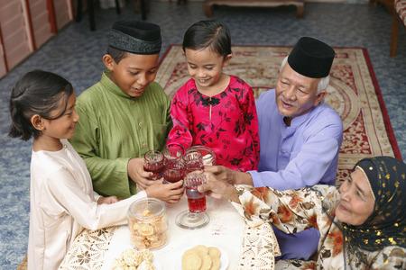 Älterer Mann und Frau Toasten Rosensirup mit ihren Enkeln