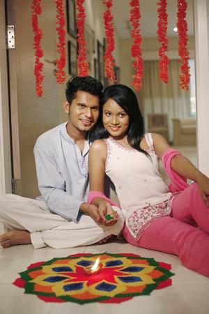 kurta: Man and woman drawing kolam together
