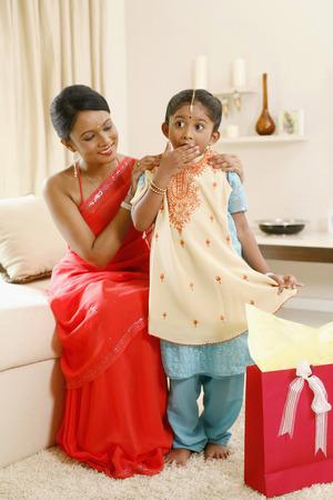 niños vistiendose: Muchacha que consigue regalo sorpresa de su madre