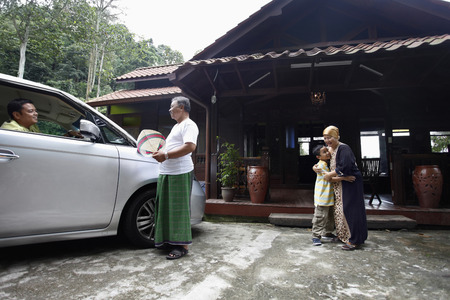 Senior man and woman standing at house compound, greeting man and boy Stock Photo