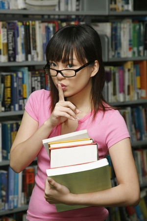 college life: Woman holding a stack of books with finger on her lips