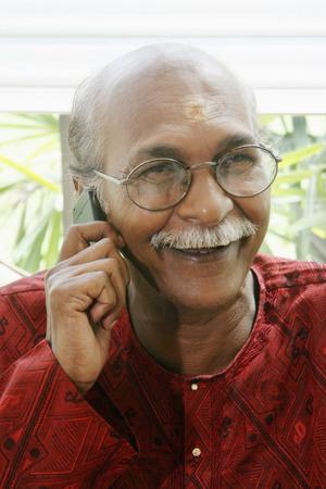 kurta: Senior man with glasses talking on the phone