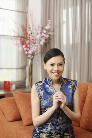 clasped: Woman in cheongsam with hands clasped wishing Happy Chinese New Year